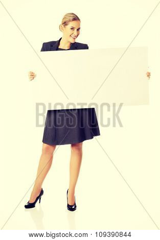Happy businesswoman holding empty billboard