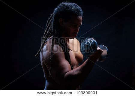 Muscular man with dreadlocks exercising in gym