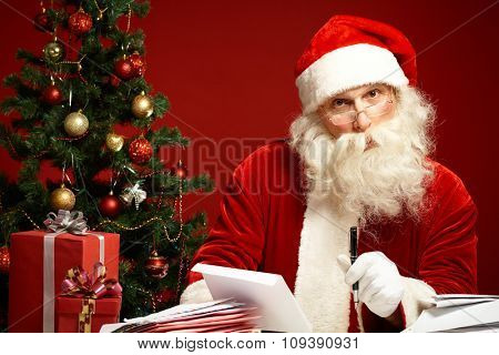 Santa answering Christmas letters by decorated fir-tree
