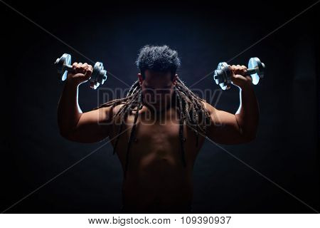 Strong man with dreadlocks working out in gym