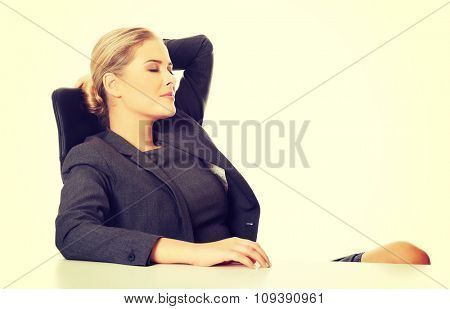 Happy businesswoman relaxing on armchair