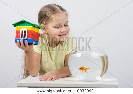 The Four-year Girl Sits With A Toy House In Front Of A Goldfish