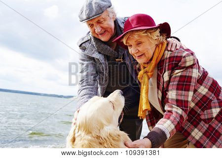 Retired couple cuddling their pet outdoors