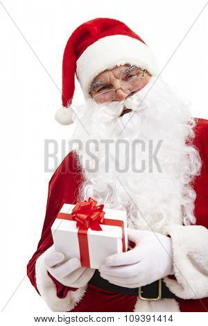 Santa Claus holding red gift-box and looking at camera