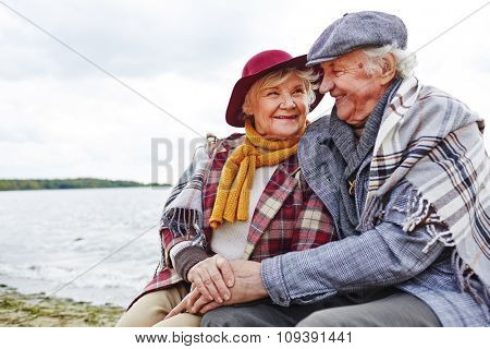 Cheerful and affectionate seniors sitting by seaside in autumn