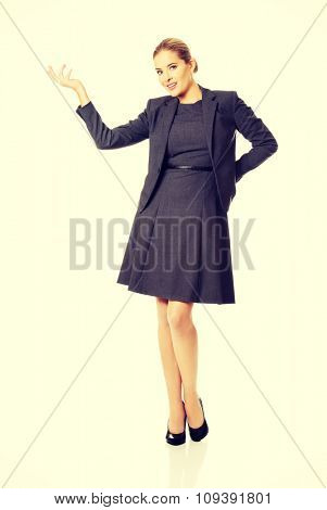Happy businesswoman presenting copy space.