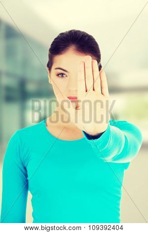 Hold on, Stop gesture showed by young woman.