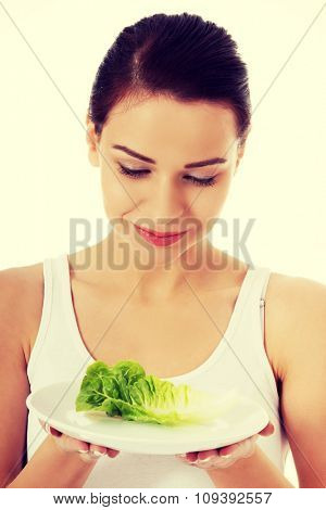 Portrait of a woman holding plate with lettuce.