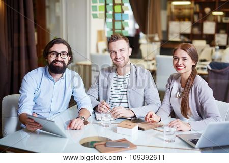 Modern businessmen and businesswoman looking at camera with smiles