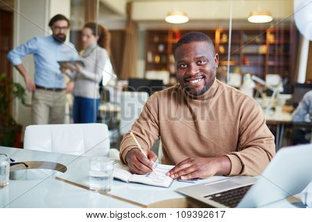 Happy African-American employee working in office