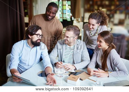Bearded businessman with touchpad explaining his idea to co-workers