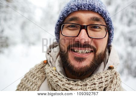Happy Asian guy in winterwear looking at camera outside