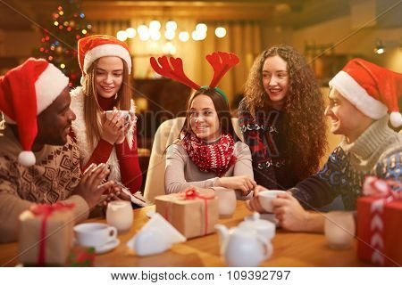 Group of happy friends talking on Christmas evening