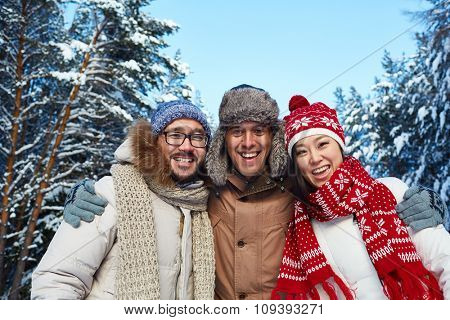 Happy friends in winterwear looking at camera outdoors