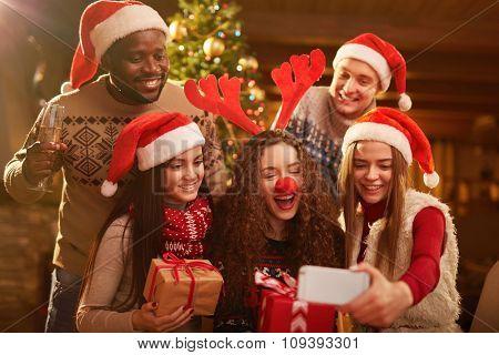 Joyful friends making selfie on Christmas evening