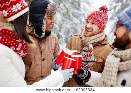 Joyful friends with hot drinks spending time in winter environment
