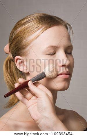 Beautiful Blond Model Applying Blusher On Cheeks