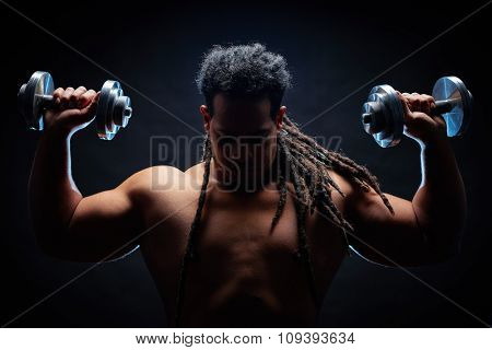 Strong and active young man with dreadlocks working out with barbells
