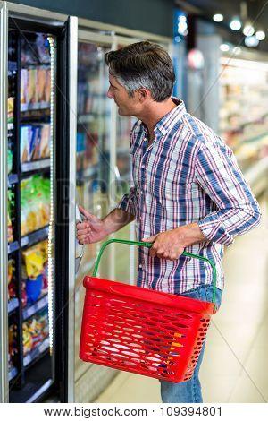 Side view of man opening supermarket fridge