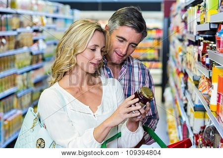 Couple reading nutritional values of food at supermarket