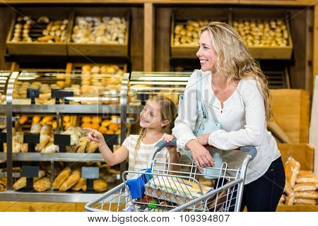 Daughter pointing and mother smiling at supermarket