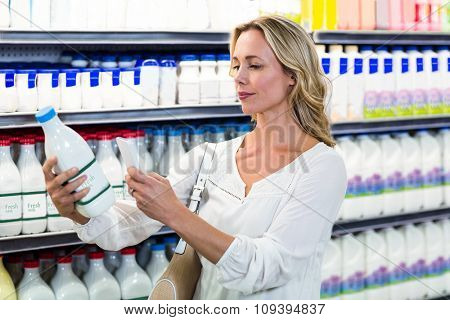 Beautiful woman taking a picture of milk bottle at the supermarket