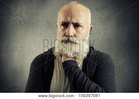 portrait of despondent senior man over grey background