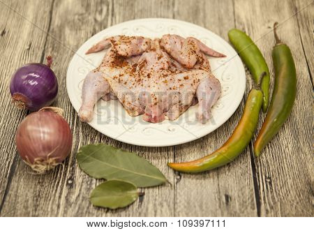 Raw fresh chicken on porcelain plate with lemon onion and chilli  on the wooden background.