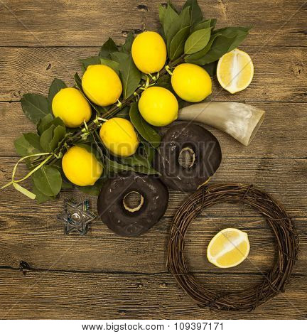 Branch lemons  donuts and goat horn. Symbols of the great holiday of Hanukkah. On wooden background