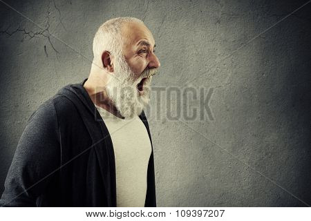 portrait of emotional screaming man with empty copyspace for your text over grey wall