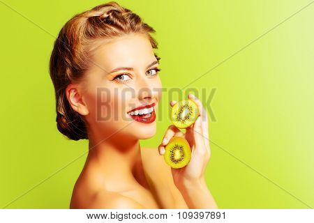 Charming young woman holding fresh juicy kiwi and smiles. Green background. Tropical fruits. Healthy eating. Beauty, cosmetics.