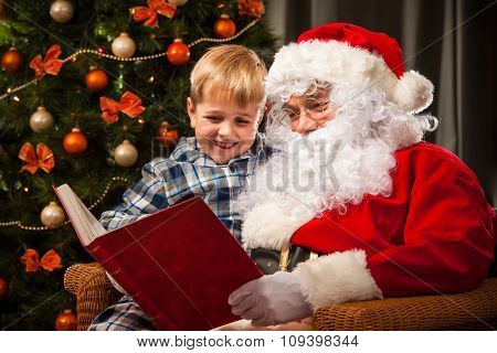 Santa Claus and a little boy reading together a book or list in front of Christmas Tree