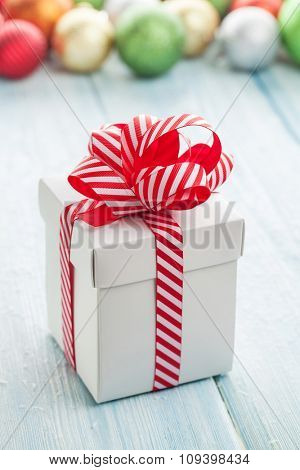 Christmas gift box and colorful baubles decor on wooden table