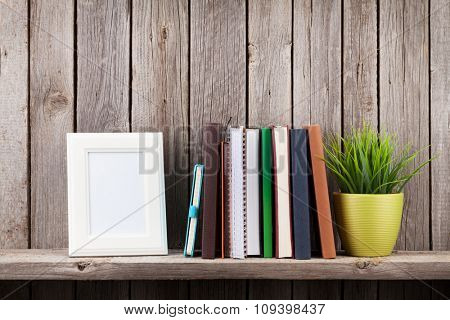 Wooden shelf with photo frames, books and plant in front of wooden wall. View with copy space