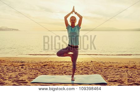 Girl In Yoga Pose Of Tree On Beach
