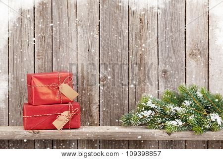 Christmas gift boxes and fir tree toy in front of wooden wall. View with copy space