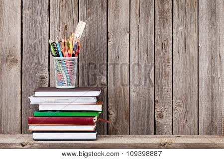 Wooden shelf with books and supplies in front of wooden wall. View with copy space