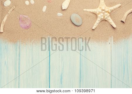 Sea sand with starfish and shells on wooden table. Top view with copy space. Toned