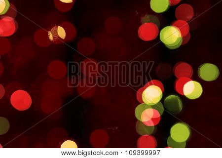Abstract Blured Background Of Dark Multi Colored Shiny Christmas Tree Decorations At Night Warm Filt