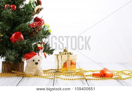 Christmas Tree, Gold Gift Box, Balls, Toy Bear, Candies And Decorations On Retro Vintage White Table
