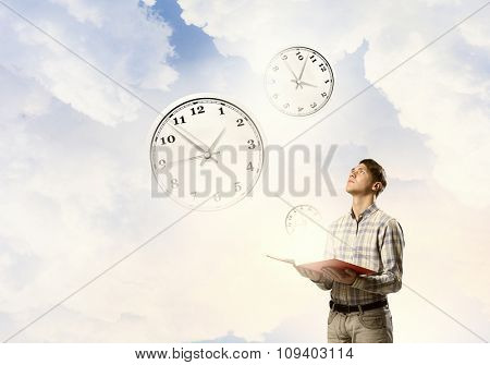 Young man with book in hands looking at clock