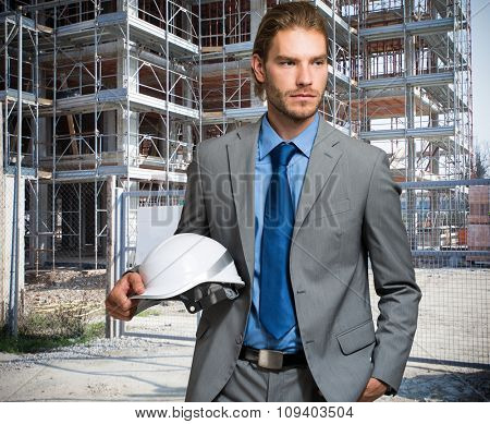 Portrait of an handsome engineer in front of a construction site