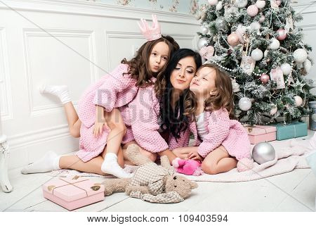 Young woman with two girls near the Christmas tree among the gifts and toys