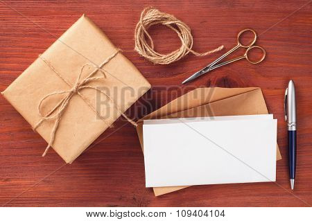 Gift Box And Envelope With Blank Paper Sheet Decorated Accessories On Wooden Table