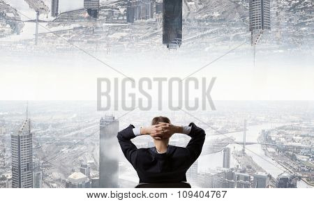 Rear view of businessman sitting on chair with hands on head