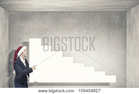 Woman in Santa hat pointing with finger at blank banner. Place for your text