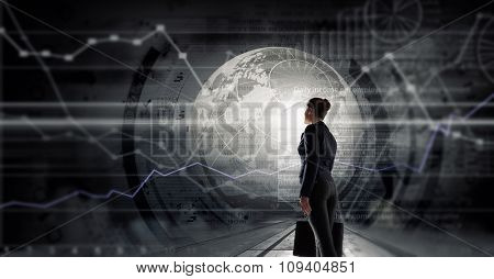 Back view of businesswoman with suitcase in hands looking at virtual panel