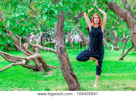 Barefoot Woman Practices Yoga In The Park Among The Trees