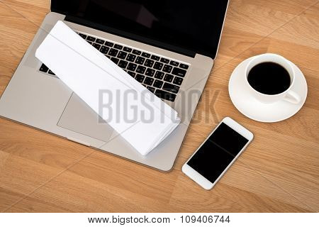 laptop with coffee cup  and smart phone,newspaper on wood table