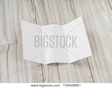 Trifold white template paper on wood texture